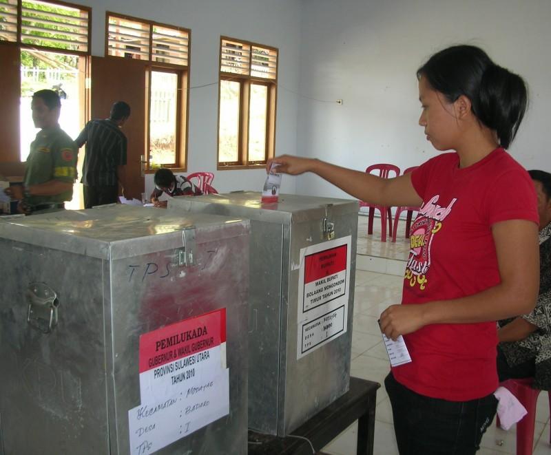 Seorang pemilih memasukan kertas ke kotak suara dalam pemilihan kepala daerah di Sulawesi Utara. (Foto: Kandi)