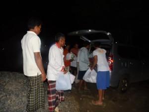 Warga menurunkan barang bantuan dari mobil. (Foto: Kandi)