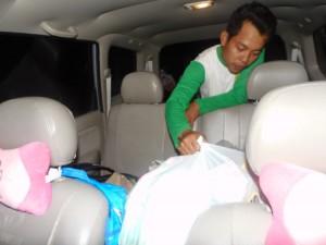 Seorang warga mengeluarkan barang bantua dari dalam mobil. (Foto: Kandi)