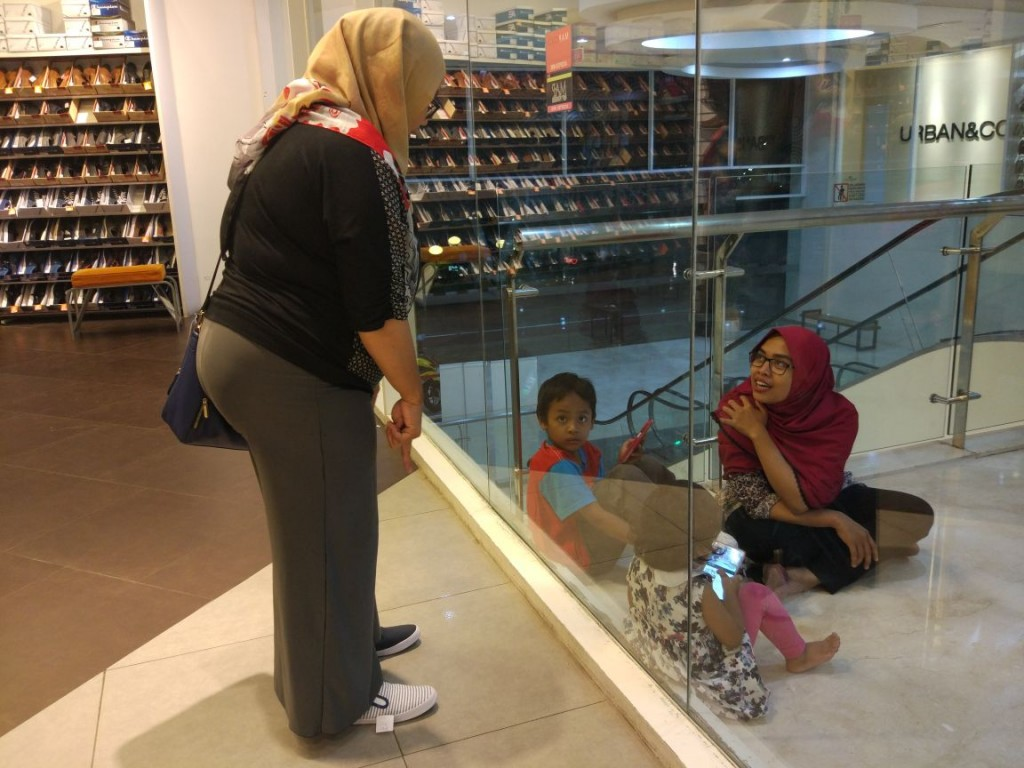 Aty (di dalam kaca) meminta saran kepada Maul (di luar kaca) tentang sepatu mana yang cocok: model selimut (kanan) atau polos (kiri). (Foto: Kandi)